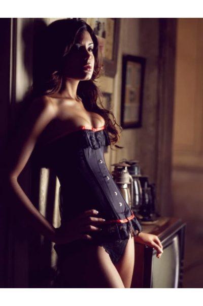 Vacker svart korsett med spetskanter och röda band